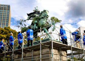 楠木正成像に付いた汚れを竹で落とす「皇居の楠公像を愛でる会」のメンバーら=20日午後、東京都千代田区