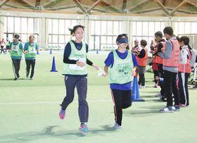 伴走者(左)とロープで結ばれ、アイマスクして走る参加者=松本市空港東のやまびこドームで