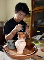 地元産のヒノキで酒器を作る金山智則さん=伊佐市の「e-Gaなんちゅう」