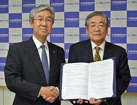 協定書を手に握手を交わす岡島理事長(右)と中田理事長