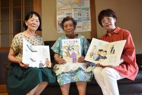 完成した絵本を手にする齋田嘉子さん(中央)と三浦知子さん(右)、緒方ヒロ子さん