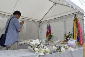 献花台で手を合わせる男性=20日、京都市伏見区