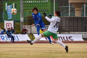 シュートを放つオルカ鴨川の村岡選手(左)=21日、鴨川市陸上競技場