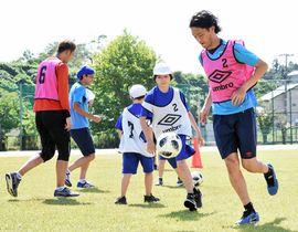 高萩選手(右)らとサッカーを楽しむ児童