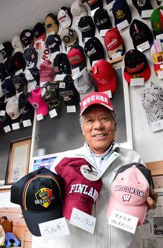 娘婿から贈られた世界各国の野球帽を手に持つ福重さん