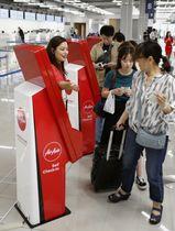 中部空港に開業したLCC向けの第2ターミナルで、手荷物預け入れを自動で行う機械を利用する人たち=20日午前