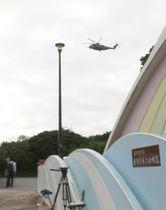 18日午前、避難訓練の合間に市立普天間第二小近くを飛行する米軍ヘリコプター。午後には別の機体が小学校上空を飛行したと防衛省が発表した=沖縄県宜野湾市