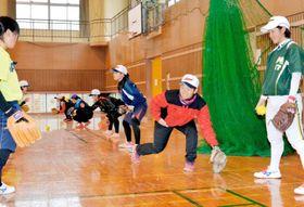 西条市での合宿中に高校生を指導する太成学院大女子ソフトボール部の部員(右から2人目)ら