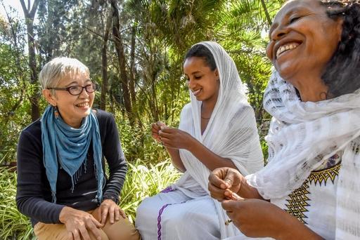 「あら、いいわね」。コーヒー豆でイヤリングなどのアクセサリーを作る女性グループに話しかける白鳥くるみ(左)。白鳥の支援もあり、品質は向上し売れ行きも伸びている=アディスアベバ(撮影・中野智明、共同)