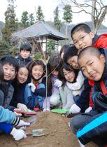 福島県で育てられた桜の苗木を植樹する子どもたち=15日午前、京都市の大覚寺