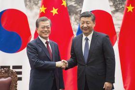 調印式典で握手を交わす韓国の文在寅大統領(左)と中国の習近平国家主席=14日、北京の人民大会堂(共同)