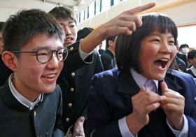 自分の番号を見つけ喜ぶ受験生=長崎市、長崎南高