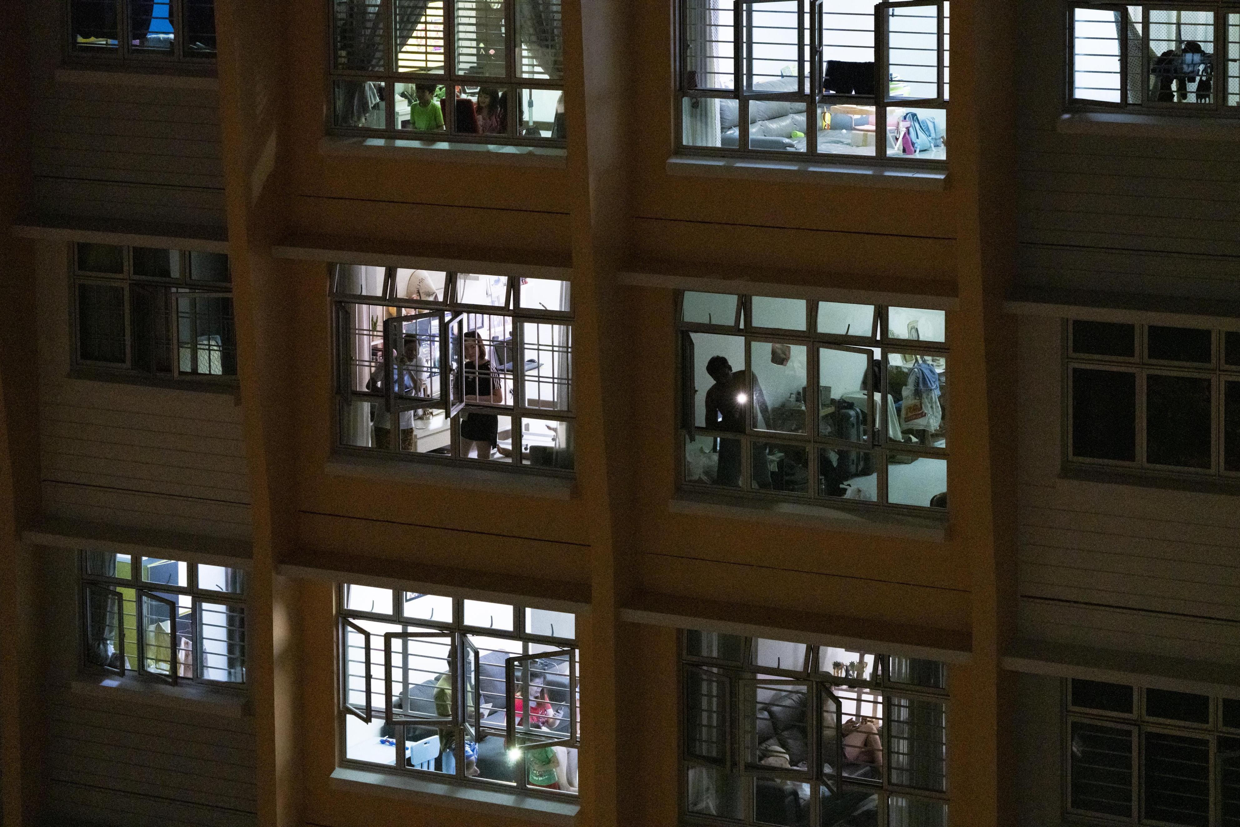 窓辺に集まって歌う住人たち=25日、シンガポール(ゲッティ=共同)