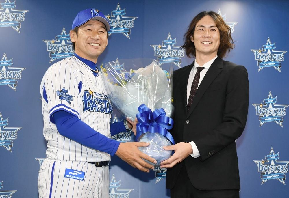 引退会見でDeNA・三浦大輔監督(左)から花束を贈られる石川雄洋さん=3月21日、横浜市内の球団事務所(代表撮影)