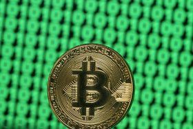 画面の上に置かれた仮想通貨「ビットコイン」のマーク(ロイター=共同)