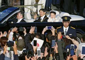 即位を祝うパレードで、沿道の人たちに手を振られる天皇、皇后両陛下=10日午後3時25分、東京都港区