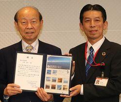 切手シートを贈呈した山根支社長(右)と石井知事=県民会館