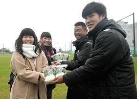岐阜大の学生から袋詰めされた米を手渡されるFC岐阜の(右から)青木翼選手と大木武監督=岐阜市曽我屋、市北西部運動公園