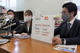 会見で研究成果を発表する成冨さん(中央)=長崎市役所
