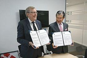 署名した覚書を掲げる加藤市長(右)とラーセン会長=15日、コペンハーゲン