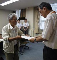 要望書を手渡す市民団体のメンバー(左)=18日午後、県庁