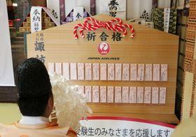 奉納された大絵馬と願い札をおはらいする神職=長崎市、諏訪神社