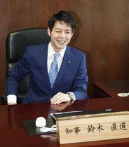 知事室のいすに座り笑顔を見せる北海道の鈴木直道知事=23日午前、北海道庁