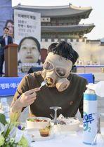「PM2.5」対策を訴えるイベントで、マスクを着けて食事をする人=14日、ソウル(共同)