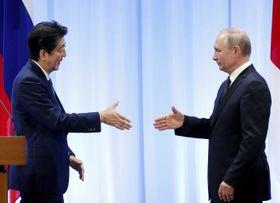 首脳会談後の共同記者発表で握手する安倍首相(左)とロシアのプーチン大統領=6月29日、大阪市(ロイター=共同)