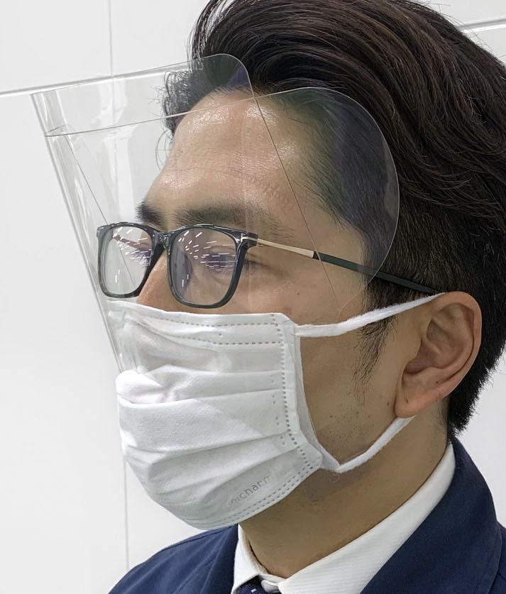 「マスクにつけれるアイシールド」を着ける高津紙器の高津俊一郎社長