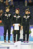 スピードスケートW杯第1戦、女子団体追い抜きを世界新で制し、表彰台で笑顔を見せる日本。左から高木美帆、佐藤綾乃、高木菜那=10日、ヘーレンフェイン(ゲッティ=共同)
