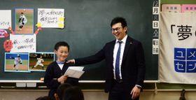 自分の夢を発表した子どもに、ねぎらいの言葉を掛ける横浜DeNA・山崎康(右) =東京・台東区立忍岡小