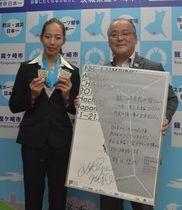 市民らに向けた感謝のメッセージを中山一生市長(右)に託した野口啓代選手=8月29日、龍ケ崎市役所