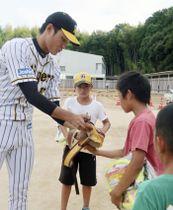 岡山県倉敷市真備町地区の避難所を訪れ、子どもたちにサインをするプロ野球阪神の藤浪晋太郎投手=20日午後