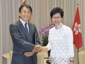 握手する斎藤農相(左)と香港政府トップの林鄭月娥行政長官=17日、香港(共同)