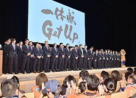 今季のスローガン「一体感GetUp」を示し、壇上に並ぶAC長野の選手たち