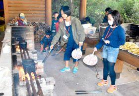 飯ごう炊さんで火加減を調節する子どもたち=16日午後、松山市西野町