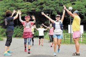 宮城県松島町のゴール地点に到着し、仲間とハイタッチする波多野さん(左から2人目)=8月24日午後4時55分ごろ
