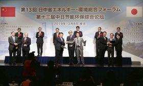 日中省エネルギー・環境総合フォーラムで、協力案件について合意文書を交わす関係者ら=8日、東京都内