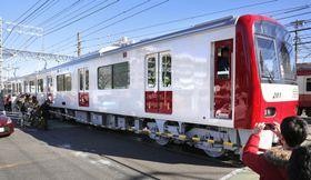 試運転のため総合車両製作所を出発する、車体側面が白いままの京急電鉄の車両=14日午前、横浜市