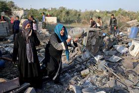 パレスチナ自治区ガザで、イスラエル軍の空爆で破壊された家を調べる女性ら=14日(ロイター=共同)
