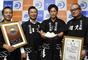 コンクールで最高賞を獲得したコメでつくったおにぎりをPRする梶原雅嗣さん(左から3人目)ら=5日午後、西予市役所