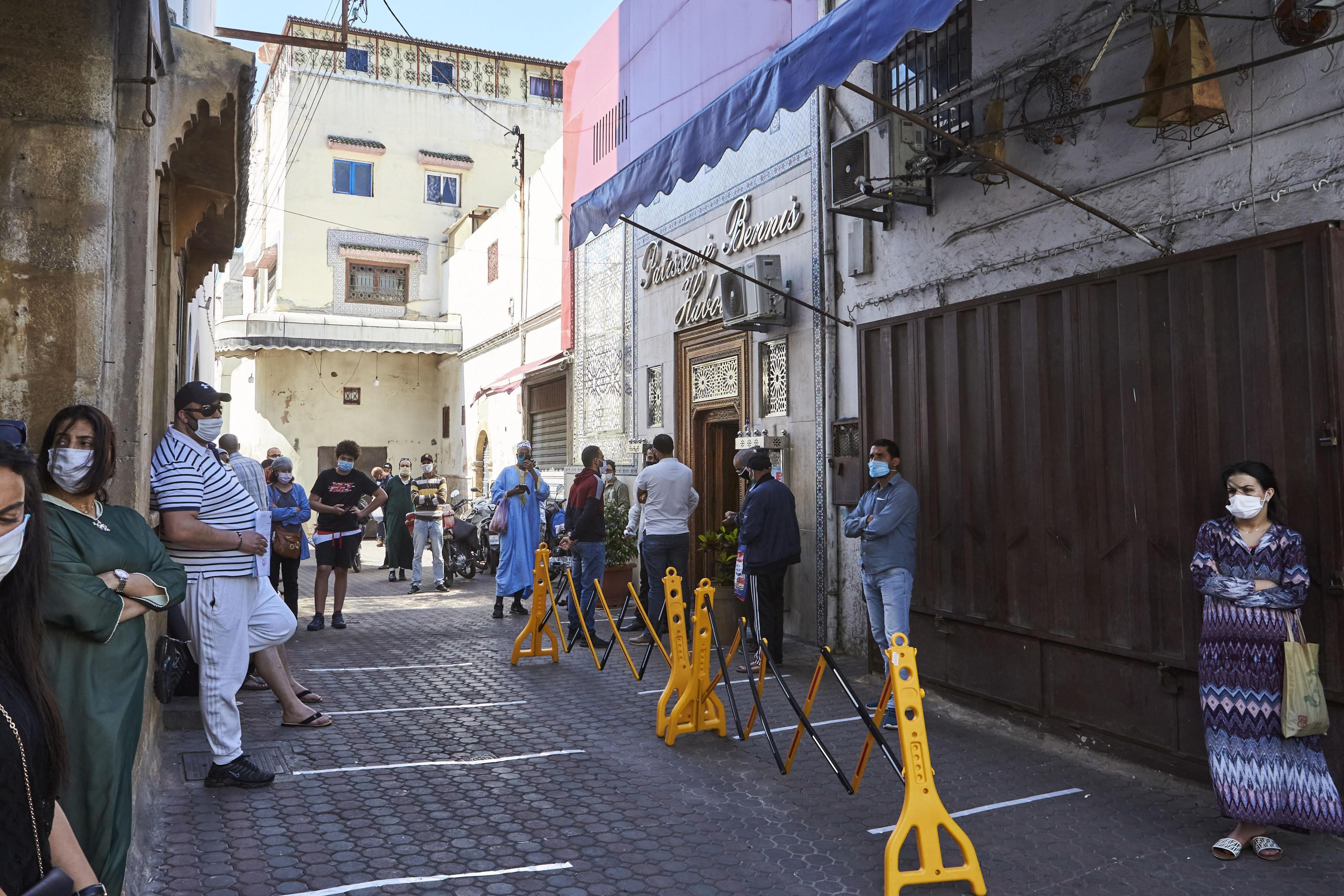 23日、モロッコ・カサブランカで、マスクを着用して洋菓子店の前に並ぶ人々(AP=共同)