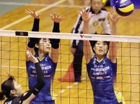 第1セット、2枚ブロックに跳ぶ岡山シーガルズの渡辺真恵(左)と川島亜依美=山陽ふれあい公園体育館