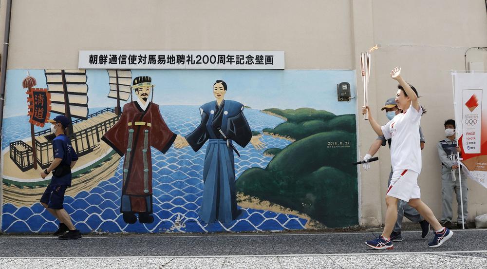長崎県対馬市でゴール地点の朝鮮通信使との交流を描いた壁画に到着した聖火ランナー=8日午後