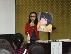 写真を手に、香澄さんが生前に残した言葉を紹介した小森さん=16日、南下浦市民センター