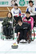 ストーンを投じる鈴木選手。後方で車いすを支えるのは赤沢選手(中川明紀撮影)
