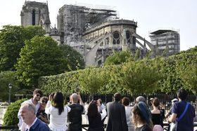 大火災に見舞われたノートルダム寺院を撮影する観光客ら=22日、パリ(共同)