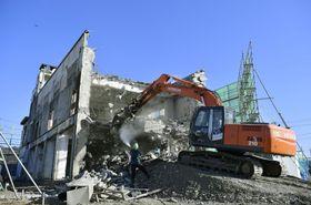 大型重機を使い解体される岩手県大槌町の旧役場庁舎。東日本大震災で28人が犠牲となった=19日午後