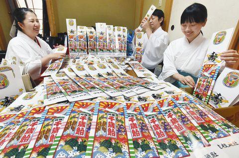 千歳飴の袋詰め作業に精を出す神職ら=福井市の佐佳枝廼社で